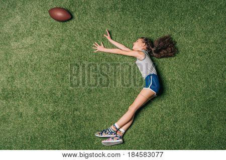 Top View Of Little Sportive Girl Catching Rugby Ball On Grass, Athletics Children Concept