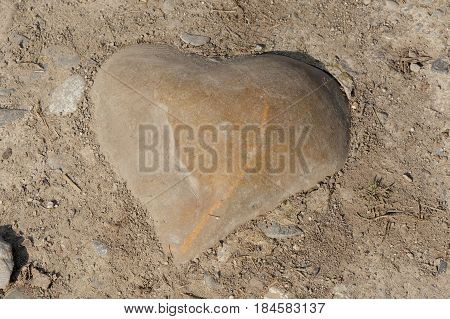 a stone in the shape of a heart in the ground