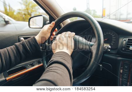 the driver keeps hands on the wheel of a car and honking his horn
