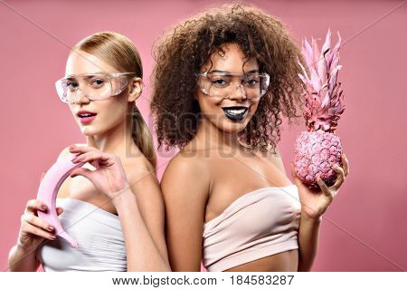 Life is fruity. Waist up portrait of smiling blonde and african girls with safety eyewear holding banana and pineapple, isolated on pink background