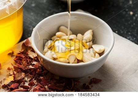 Peeled Raw Peanuts In A White Ceramic Bowl Poured With Thin Honey Trickle
