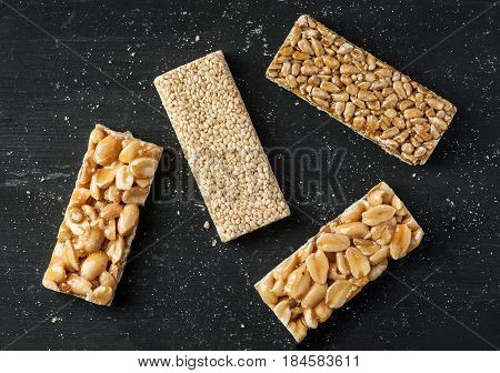Peanut, Sesame And Sunflower Seed Brittle On A Black Wooden Table, Top View, Flat Lay