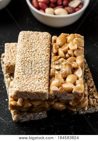 Sesame And Peanuts Bars Stacked On A Black Wooden Table Closeup Shot, Vertical