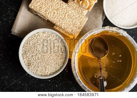 Honey Jar With Metal Spoon In It, Sesame Seeds In A White Bowl And Few Brittle On A Wooden Table, To