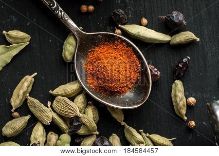 Ground Paprika In A Metal Spoon With Cardamon Seeds Around On A Black Wooden Table, Selective Focus,