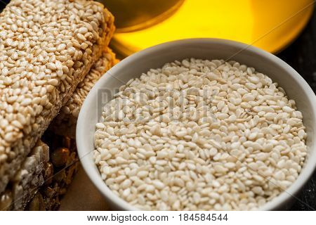 Sesame Seeds In A White Ceramic Bowl And Few Brittle With Honey Jar, Closeup Shot