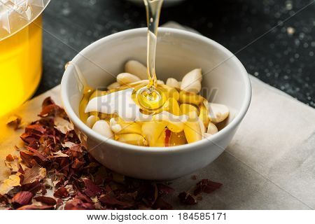 Raw Peanuts In A White Ceramic Bowl Poured With Thick Honey Trickle