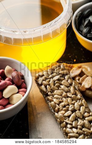 Peanut And Sunflower Seeds Brittle With Honey Jar And Raw Ingredients In The White Ceramic Bowls, Ve