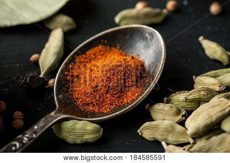 Ground Paprika In A Metal Spoon With Cardamon Seeds Around On A Black Wooden Table, Selective Focus