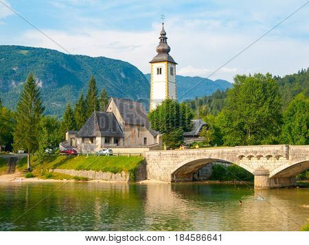Church of St John the Baptist and old stone bridge at Lake Bohinj in alpine village Ribicev Laz, Julian Alps, Slovenia.