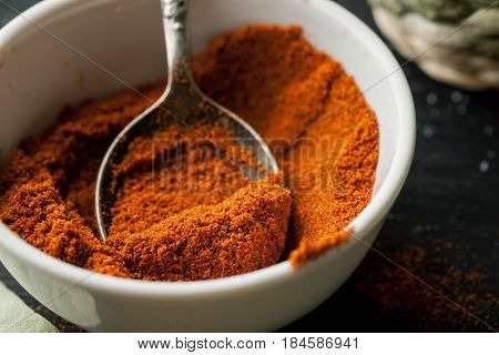 Ground Paprika Powder In A White Ceramic Bowl With Metal Spoon In It, Macro Shot, Selective Focus