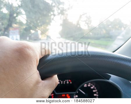 The man's hand is steering the car steering wheel.