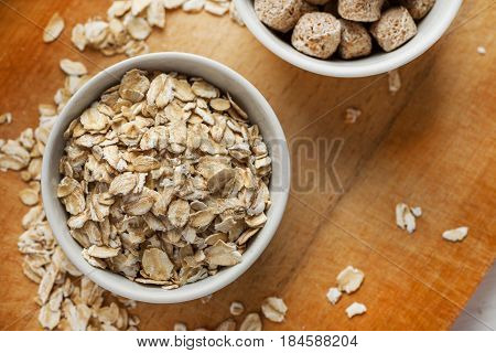 Oat Flakes And Wheat Bran In Ceramic Bowls On A Wooden Table, Top View