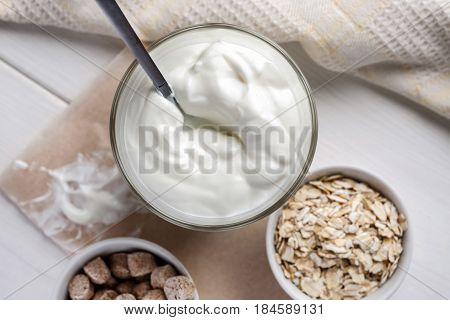 Yogurt With Wheat Bran And Oat Flakes On A Wooden Table, Top View