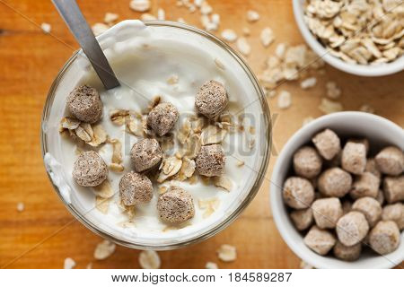 Yogurt In Glass With Oat Flakes And Wheat Bran In It, Selective Focus, Top View