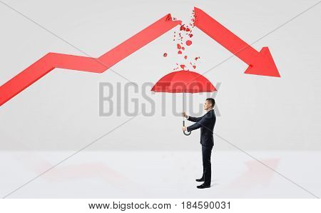 A tiny businessman hiding under a red umbrella from the rubble of a broken red statistic arrow. Business result. Success and failure. Surviving bankruptcy.