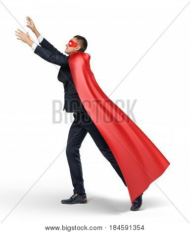 A businessman in a red flowing cape standing in side view and trying to grab something above with both hands. Business and success. Efforts and results. Catching best deals.
