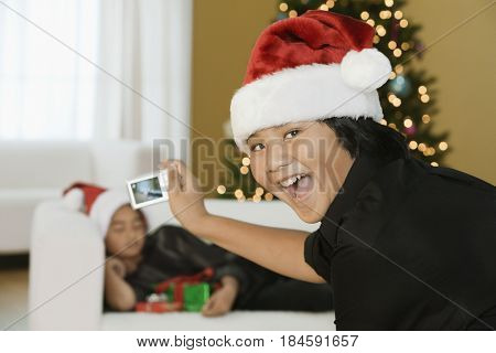 Filipino boy taking picture of brother at Christmas time