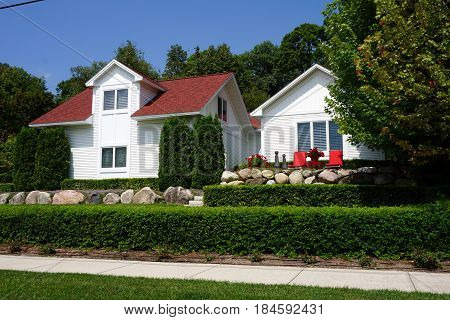 An elegant white home, with carefully manicured shrubbery, on Fourth Street in Harbor Springs, Michigan during August.