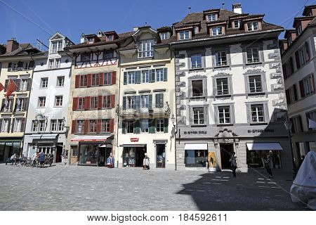 Lucerne Switzerland - May 06 2016: Buildings with decorative facades where on the ground floor operates outdoor seating restaurant and there are various stores. A few people can be seen there.