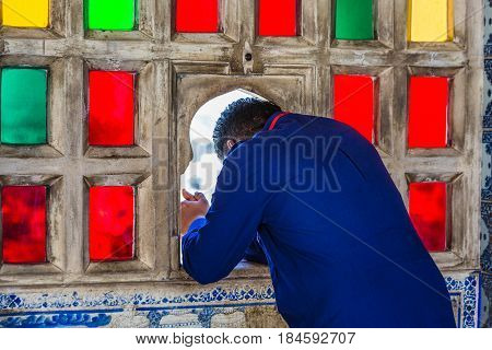Man looking  through stained glass window at Udaipur castle, India.