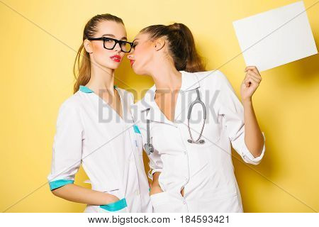 women doctors or pretty nurses lesbian girls in white medical coats going to kiss on red sexy lips on orange background. Sexual attraction to sex. Empty paper sheet in hand copy space