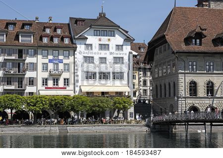 Lucerne Switzerland - May 08 2016: Houses by the riverside and the alley along the shore which is planted with trees under which is an outdoor seating restaurant there are also some people.