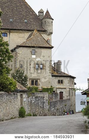 Yvoire France - May 24 2013: Medieval castle that is beautifully situated by the lake and next to it a narrow street leads to the shores of Lake Geneva