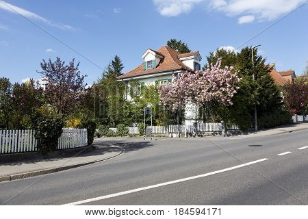 Bern Switzerland - April 14 2017: Residential houses hidden among the lush vegetation of many bushes and trees on a narrow street in a quiet district. White fences of the property can be seen.