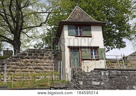 Rapperswil Switzerland - May 10 2016: The small house with green door and shutters is located at the wall that surrounds the castle grounds. The building looks like a watchtower