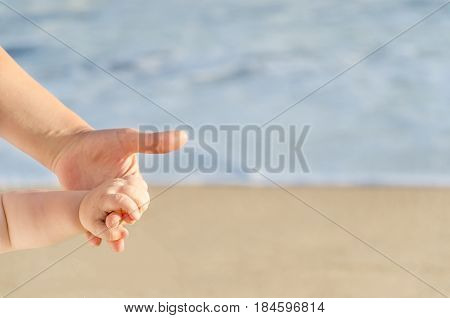 Mother is holding child's hand on the sandy beach near ocean in sunny day/Mothers day concept