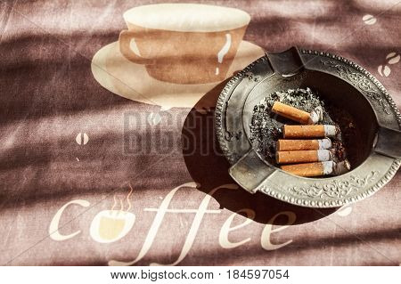 Various cigarette butts in full ashtray on table