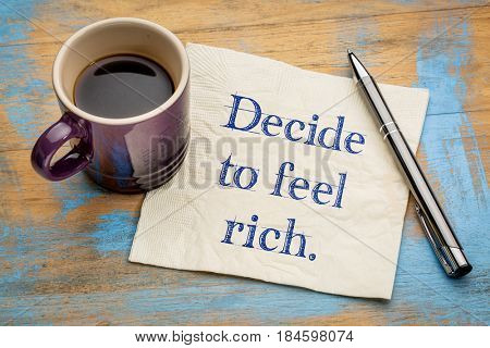 decide to feel rich advice - handwriting on a napkin with a cup of coffee