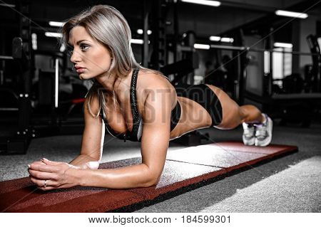 Beautiful Caucasian Young Woman Doing Plank Exercise In The Gym