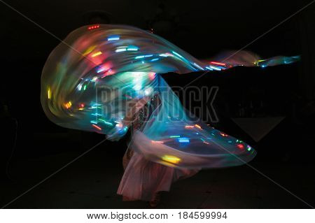 Woman dancing in dark with fluttering dress and colorful lights on her