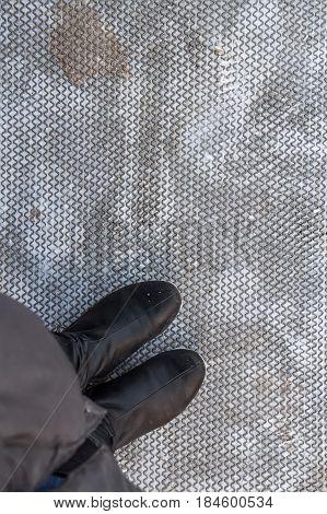 Closeup female feet in balck boots standing on grey rubber mat