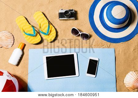 Summer vacation composition with tablet, smart phone, a pair of yellow flip flop sandals, hat, sunglasses, sun screen and other stuff on a beach. Sand background, studio shot, flat lay, copy space.