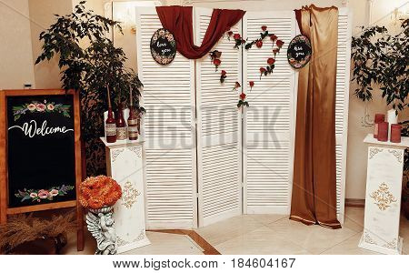 Wedding Photo Booth Zone And Welcome Board. Rustic Wooden Wall With Flowers, Red Roses Heart And Lov