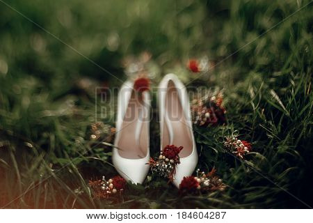 Beautiful White Shoes With Red Bouquets On Green Grass In The Morning. Space For Text. Bride Getting