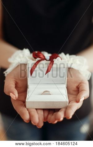 Wedding Morning Preparation Concept. Woman Hands In Silk Garter Holding Golden Ring In Box. Space Fo