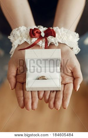wedding morning preparation concept. woman hands in silk garter holding golden ring in box. space for text