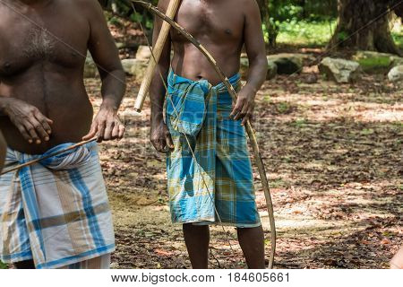 Closeup of Vedda men standing in group in waistcloths