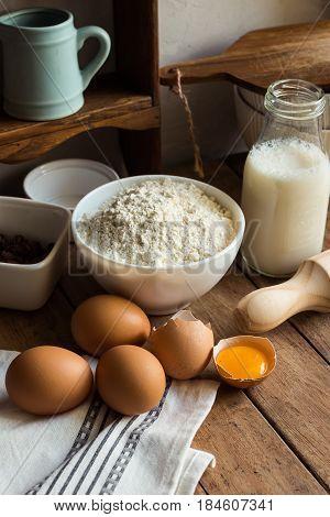 Baking ingredients flour eggs open yolk milk rolling pin cupboard raisins rustic kitchen interior utensils dishware cozy atmosphere
