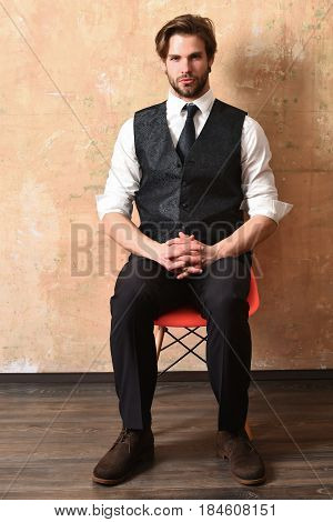 serious young fashion business man in classy suit and tie sitting straight on chair on beige background