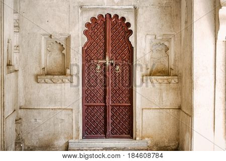 Wooden door at Udaipur castle courtyard, India.