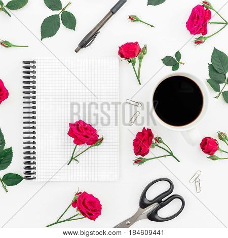Beauty blog concept. Workspace with notebook, pen, clips, scissors, coffee mug and roses on white background. Flat lay, top view. Woman workspace.