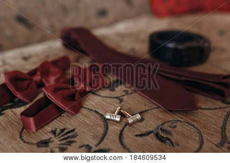 Stylish Red Bow-tie And Tie With Belt And Cufflinks On Bed. Morning Preparation For Wedding. Groom G