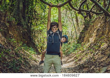 The Father Carries His Son In A Baby Carrying Is Hiking In The Forest. Tourist Is Carrying A Child O