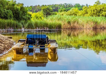 Pleasure pedal catamaran on the lake shore. Pedal boat for a quiet holiday in nature.