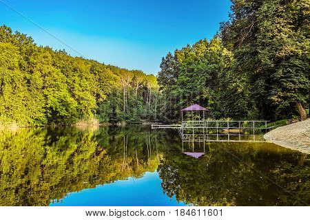 Lake in a forest with a gazebo and small pier for pleasure pedal catamaran on the lake shore. Dock for pedal boat and a quiet holiday in nature.